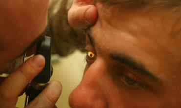 Lt. Cmdr. Lewis Fermaglich, a medical officer, examines a local man's eye in Trailer Town, Iraq.